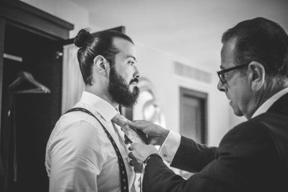 el novio poniéndose la corbata para la boda